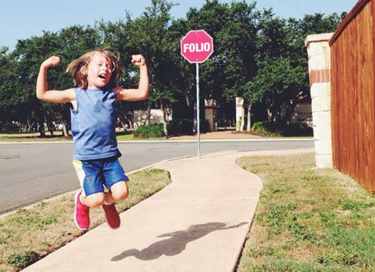 A girl jumps in the air in joy in front of a sign reading -- Folio