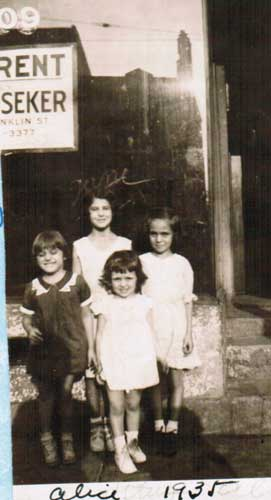"""Aisquith Stree6 (1935) - my mom and her sisters with a neighbor. There are very few photos that show the neighborhood (her house now is an empty lot according to Google Streetview). The sign behind has an address for a street that ends in """"nklin"""" -- the nearest I could find was """"Conkling St, a mile east"""