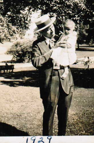 That's Harry (dandy hat!- holding my Mom as a baby, 1929. Might that be Patterson Park, near where they lived?