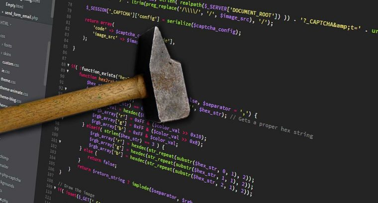 wood handled hammer held over a screen of computer code