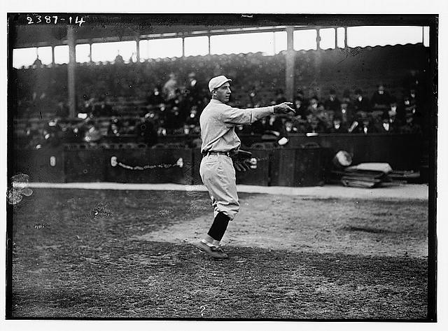 A 1900s era baseball pitcher on the mound gestures for a ball, in the bleachers behind are mostly men in dark suits.