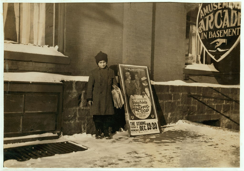 Old time photo of boy in ski hat and overcoat standing on snow covered street with newspapers under his arm