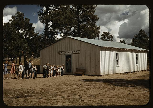 "A line of kids and a few adults, dressed as if in the times of the 1940s, are lined up to enter a meta shed structure bearing the label ""Farm Bureau"""