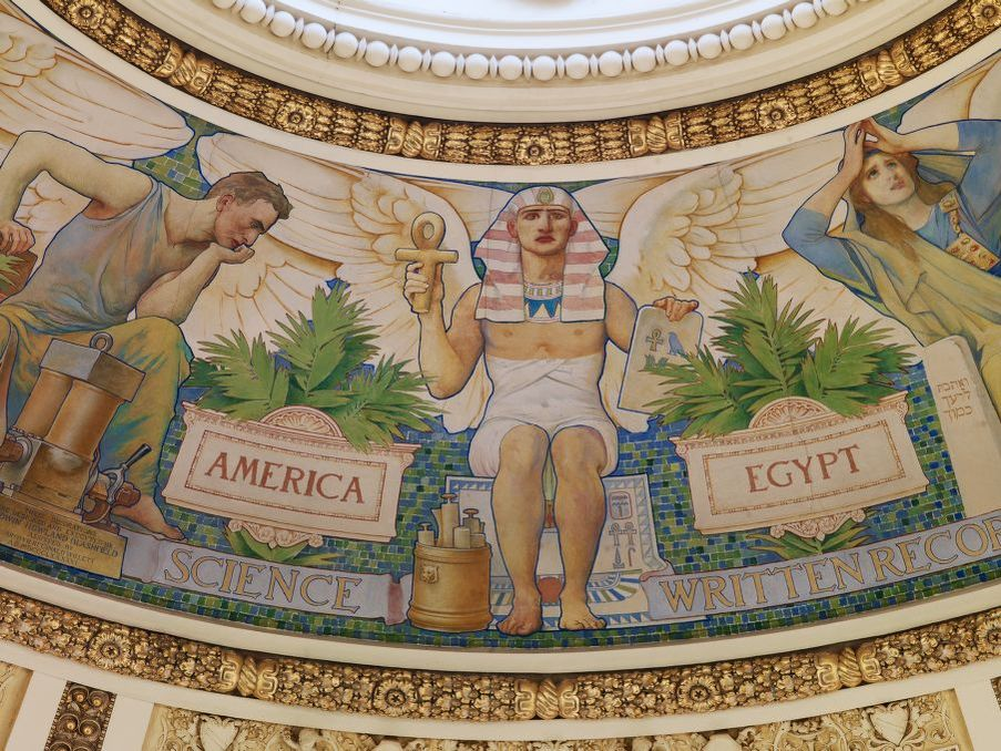 "Mural images on the dome of a building with a thinker type pose labeled ""America"" and a Pharaoh like figure labeled ""Egypt"", in the latter's hand is a stone with an ankh symbol and a small blue bird"