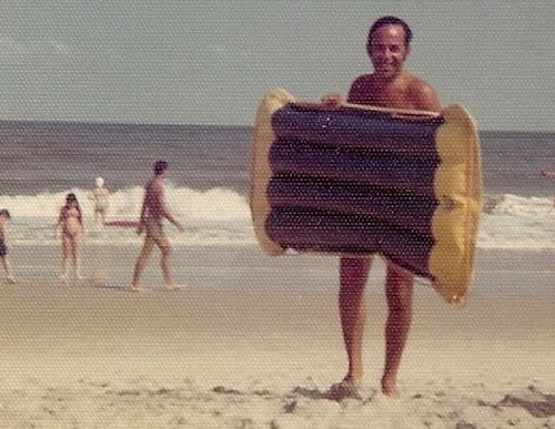 My dad smiling in the 1970s vintage photo walking in from the ocean with a surf raft.