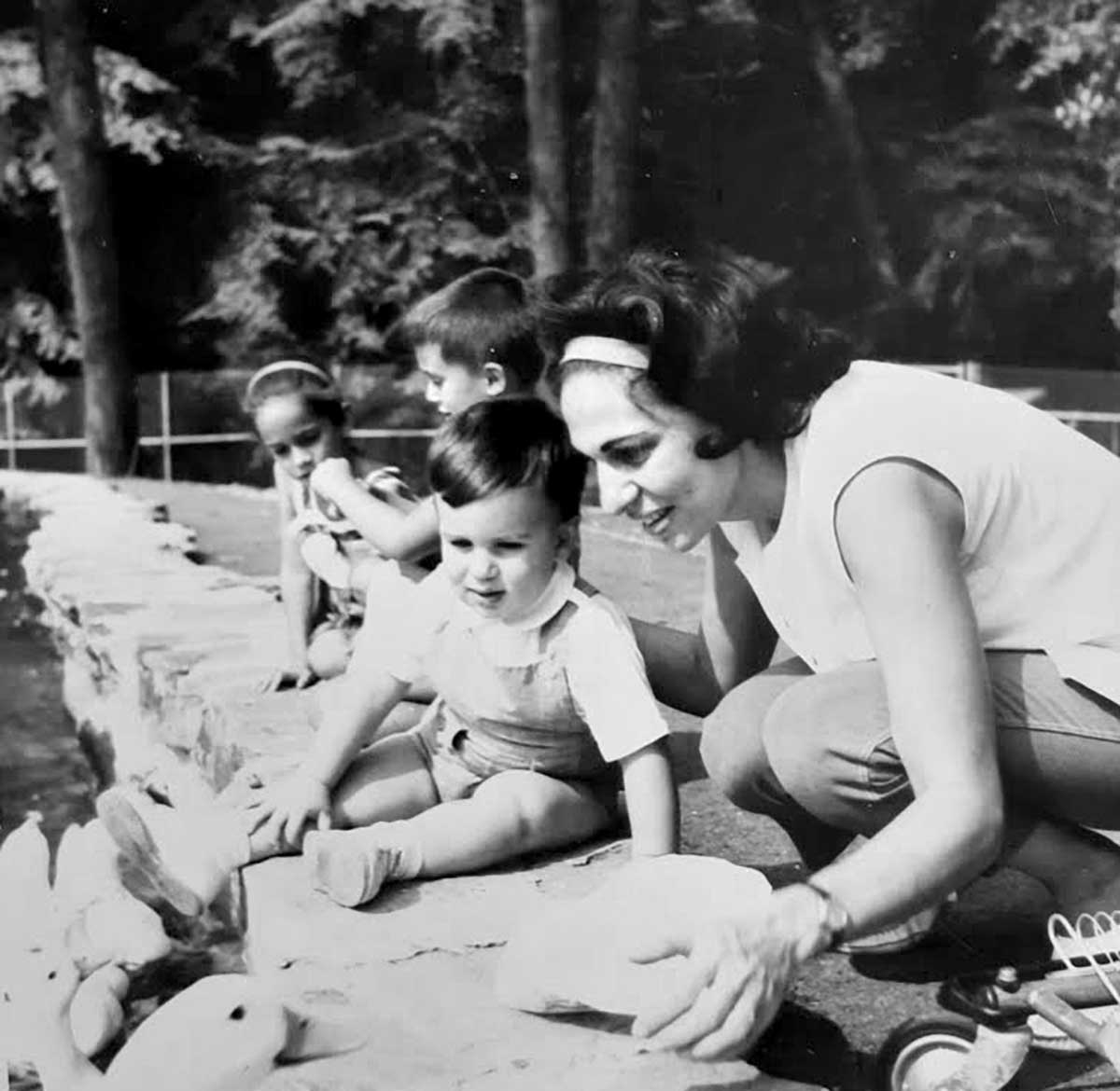 Black and white photo of my mom kneeling down next to me at age maybe 3, we both are looking at ducks in a pond.